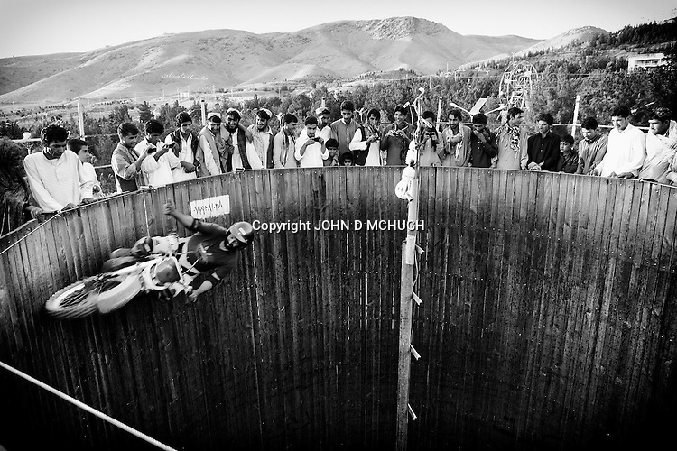 """Afghans watch a motorcycle rider perform in a """"Wall of Death"""" in a park in Herat, 20 September 2013. (John D McHugh)"""