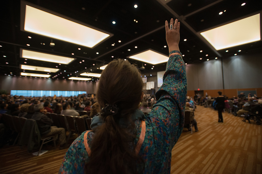 """Christina Edwin raises four fingers in support of the """"Fairbanks Four"""" during Governor Bill Walker's appearance at the 2015 Alaska Federation of Natives Convention at the Dena'ina Center."""