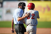 Umpire Emil Jimenez walks Auburn Doubledays Andres Martinez (32) to first after being hit by a pitch during the second game of a doubleheader against the Batavia Muckdogs on September 4, 2016 at Dwyer Stadium in Batavia, New York.  Batavia defeated Auburn 6-5. (Mike Janes/Four Seam Images)
