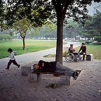 A Chinese man takes an afternoon nap as a child runs past at a park in Beijing, October 2011. (Mamiya 6, 75mm f3.5, Kodak Ektar 100 film)