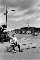 Italy. Liguria Region. Ospedaletti. A cyclist rests on a bench on the sea front. An elderly couple walks and passes near a replica of the Statue of Liberty standing onrestaurant's roof. 28.12.15 © 2015 Didier Ruef