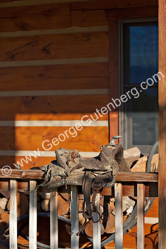 Old saddle hangs on porch rail