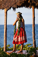 Young Hawaiian woman in hula attire in a beachfront gazebo at sunset