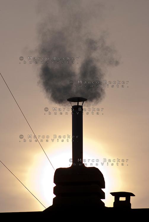 Milano, fumo da un comignolo su un tetto in periferia --- Milan, smoke from a chimney on a roof in the periphery