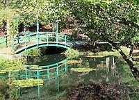 Stock photo: Small green color wooden bridge crossing a small lake in the Gibbs garden in Georgia, USA.