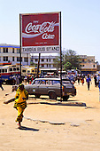 Tabora, Tanzania. Town Bus Stand with Coca Cola sign and Peugeot 505 taxi with woman in yellow wrap.