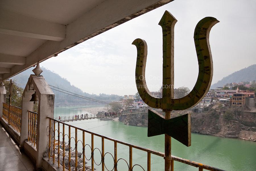 India, Rishikesh.  Trident, emblem of the Hindu god Shiva, Tera Manzil Temple.  Ganges (Ganga) River below.