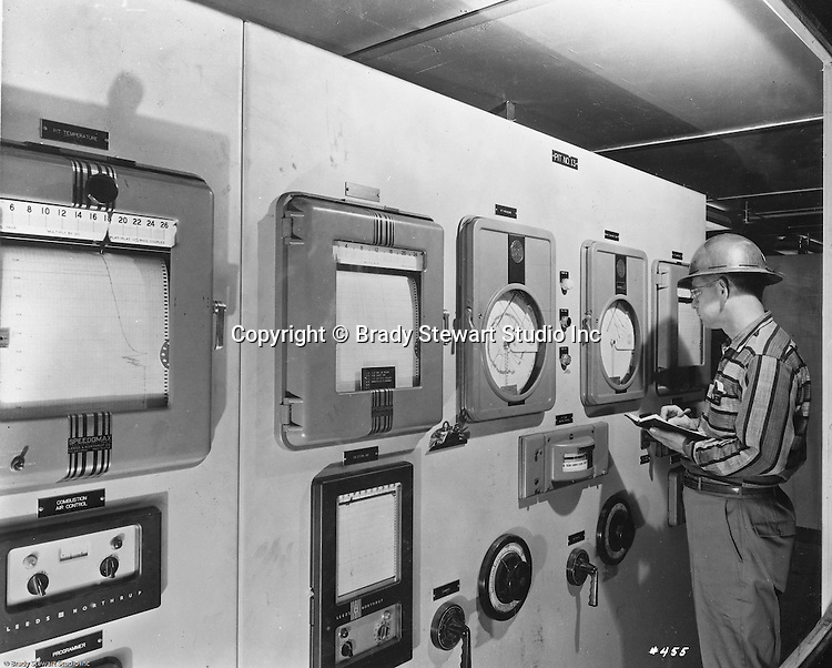 Pittsburgh PA:  View of an engineer keeping an eye on the gauges in a steel mill.