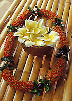 firecracker lei with kukui nut and ti leaf, with  plumeria flowers, on a bamboo table.