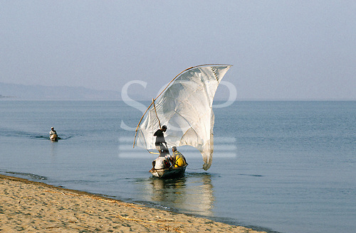 Lake Tanganyika, Tanzania. Dhow with a white patchwork sail being launched as a canoe arrives.