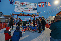 A crowd gathers around Alan Eischens in the finish chute in Nome shortly afer he arrived on Saturday March 21, 2015 during Iditarod 2015.  <br /> <br /> (C) Jeff Schultz/SchultzPhoto.com - ALL RIGHTS RESERVED<br />  DUPLICATION  PROHIBITED  WITHOUT  PERMISSION