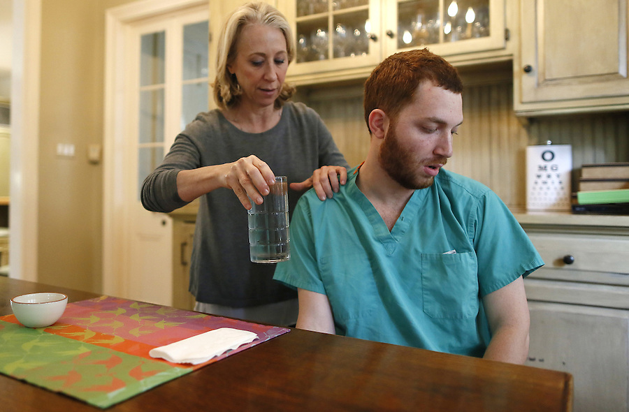 """PLEASE HOLD FOR MARTHA IRVINE STORY: In this Thursday, March 3, 2016 photo, Ellen Schneider hands her son, Ben Alexander, a glass of water after Ben took medication at their home in Metairie, La. Alexander, 22, has nonverbal autism, a condition that became apparent when he was 2 years old. He has found his voice through writing using what is known as """"facilitated communication,"""" a method in which another person steadies the hand of the autistic person, so he or she can communicate through typing. (AP Photo/Jonathan Bachman)"""