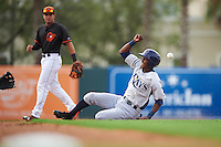 GCL Rays outfielder Miguel Hernandez (14) slides into second as Alejandro Juvier (16) looks on during the first game of a doubleheader against the GCL Orioles on August 1, 2015 at the Ed Smith Stadium in Sarasota, Florida.  GCL Orioles defeated the GCL Rays 2-0.  (Mike Janes/Four Seam Images)
