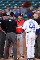 Birmingham Barons manager Julio Vinas (54) talks with Razor Shines (44) as umpires Blake Felix, Alex Ransom, and Steve Marcum listen in during a game against the Chattanooga Lookouts on April 24, 2014 at AT&T Field in Chattanooga, Tennessee.  Chattanooga defeated Birmingham 5-4.  (Mike Janes/Four Seam Images)