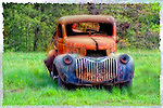 An old rusty truck sits in a field.