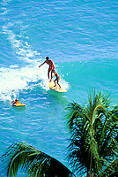 Tandem surfing in Waikiki.  Man teaching boy to surf