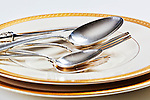 Gold Leaf White China and Sterling Silver Flatware on table with grey backdrop.