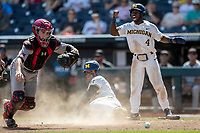 Michigan Wolverines second baseman Ako Thomas (4) celebrates as teammate Jordan Nwogu (42) is safe at home. Texas Tech Red Raiders catcher Braxton Fulford (26) scrambles for the ball during the NCAA College World Series on June 21, 2019 at TD Ameritrade Park in Omaha, Nebraska. Michigan defeated Texas Tech 15-3 and will play in the CWS Finals. (Andrew Woolley/Four Seam Images)