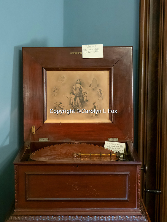 An old victrola sits in the dining room of an old house.
