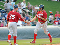 First baseman Jim Murphy (44) of the Lakewood BlueClaws is congratulated by manager Chris Truby after hitting a home run  in a game against the Greenville Drive on July 12, 2011, at Fluor Field at the West End in Greenville, South Carolina. (Tom Priddy/Four Seam Images)