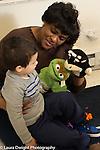 Preschool 2-3 year olds female teacher using puppet to talk to boy