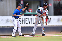 Asheville Tourists third baseman Jeff Moberg (3) and Justin Dean (14) after a play at third base during a game against the Rome Braves at McCormick Field on September 3, 2018 in Asheville, North Carolina. The Tourists defeated the Braves 5-4. (Tony Farlow/Four Seam Images)