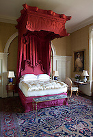 An imposing canopy of pink hangings with a carved pelmet and headboard give this bed an opulent stature in the room