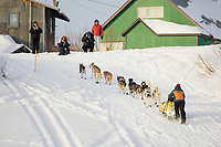 Residents and spectators watch as Sigrid Ekran runs up the bank of the Yukon river into Kaltag on Sunday morning during Iditarod 2008