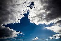 Clouds converge against a blue sky.