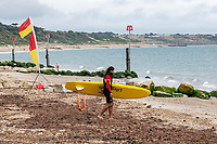 BNPS.co.uk (01202 558833)<br /> Pic: MaxWillcock/BNPS<br /> <br /> Pictured: An RNLI lifeguard walks over the mass of rotten seaweed.<br /> <br /> A south coast beach has become a no-go zone at the height of the summer holidays after a mass of rotten seaweed was allowed to fester on the sand.<br /> <br /> The vast carpet of kelp has been left to gather on Avon Beach in Christchurch, Dorset, for over a month.<br /> <br /> The unpleasant mess is attracting flies and is putting people off visiting the beauty spot which is normally hugely popular with families.<br /> <br /> Bathers are having to wade through the sticky seaweed to get to the sea and are usually left with their legs covered in it.