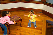 MR / Schenectady, NY. Infant in early walking stage (girl, 11 months, African American & Caucasian) exhibits 11-month-old human development milestone behavior as she balances herself and tries to reach footstool, while her sister (2, African American & Caucasian) is moving it. MR: Dal5, Dal4. ID: AL-HD. © Ellen B. Senisi
