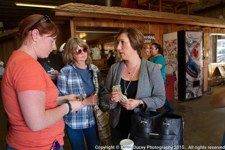 Mary Kate Fowler (left) from Lake Bay, Wash.,Rhonda Froode, and Lindsay Jackman pool their cash after Ray the pony went up for auction at the Enumclaw Sale Pavilion in Enumclaw, Wash. on May 9, 2015. Eight people banded together to raise money for Ray's rescue. Typically an older pony like Ray would go for between $50-$100 but he was sold for $625. (photo © Karen Ducey Photography)