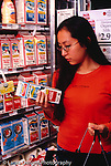 College student female shopping at supermarket, reading label on milk container