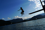Woman diving or jumping into lake from diving board, arms outstretched, wearing bikini