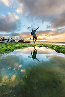 A man balances himself as he walks near a kelp-lined pond along a rocky seashore at sunset, Pua'ena Point, North Shore, O'ahu.