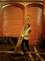 A carpenters protects a shutter in the Estafeta street before the fourth run of the bulls of the San Fermin festival, on July 10, 2012, in the northern Spanish city of Pamplona. The festival is a symbol of Spanish culture that attracts thousands of tourists to watch the bull runs despite heavy condemnation from animal rights groups. (c) Pedro ARMESTRE