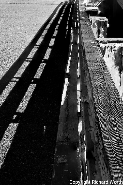 Wood grain in raised relief on a railing, and the railing's shadow - the 1933 Dardenelles Bridge, a piece of history preserved next to its contemporary replacement along Highway 108 near Sonora in the Sierra Nevada Mountains.
