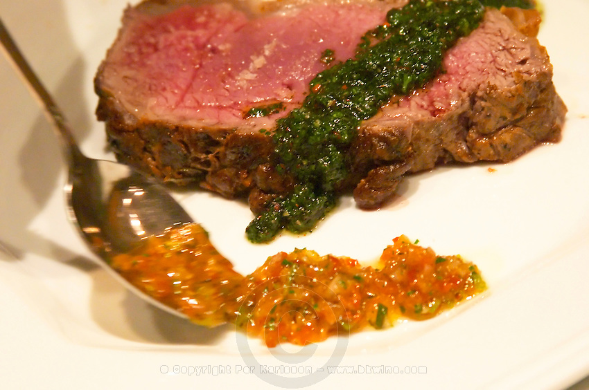A slice of juicy red roast beef with a cook placing green herb sauce on it and yellow tomato and vegetable coulis The Dolly Irigoyen - famous chef and TV presenter - private restaurant, Buenos Aires Argentina, South America Espacio Dolli