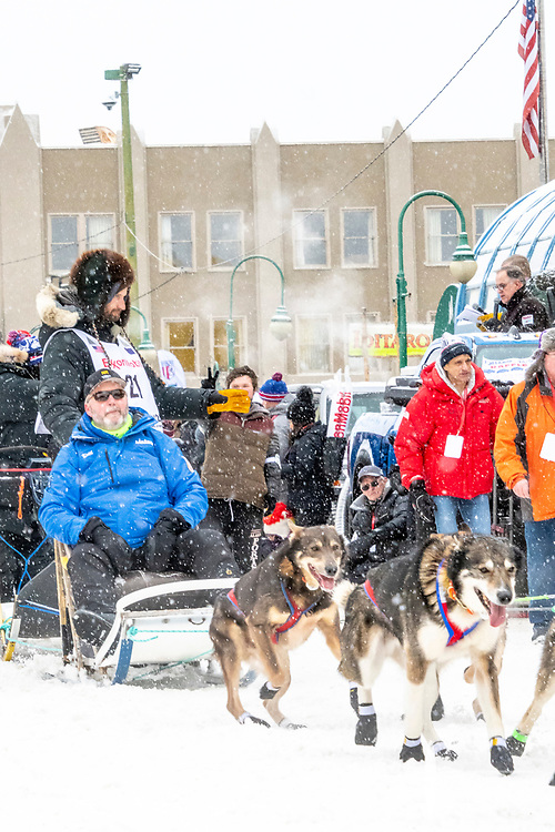 Nicolas Petit and team leave the ceremonial start line with an Iditarider and handler at 4th Avenue and D street in downtown Anchorage, Alaska on Saturday March 7th during the 2020 Iditarod race. Photo copyright by Cathy Hart Photography.com