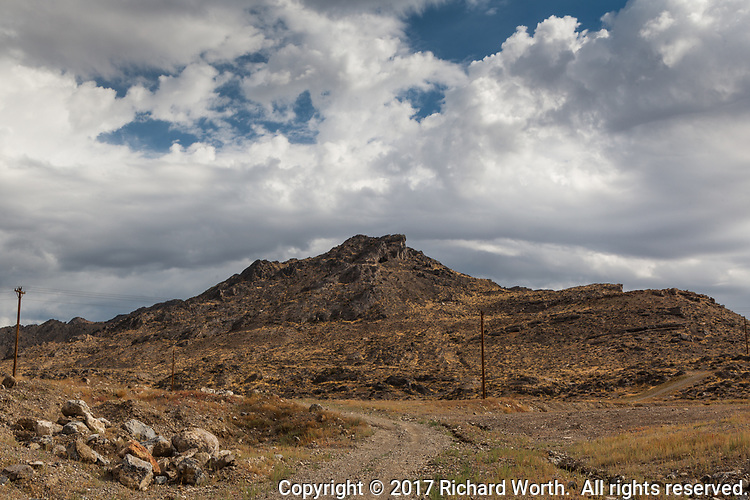 A dirt road heads toward then veers away from a craggy bluff on the outskirts of Wendover, on the Utah Nevada border.