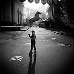 A little girl in roller-blades holding a horse balloon, in an alley at the VVC, former VDNKh. Moscow, Russia, 2009.