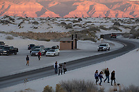 People walk from a parking area to watch the sunset at White Sands National Monument near Alamogordo, New Mexico, USA, on Fri., Dec. 29, 2017.