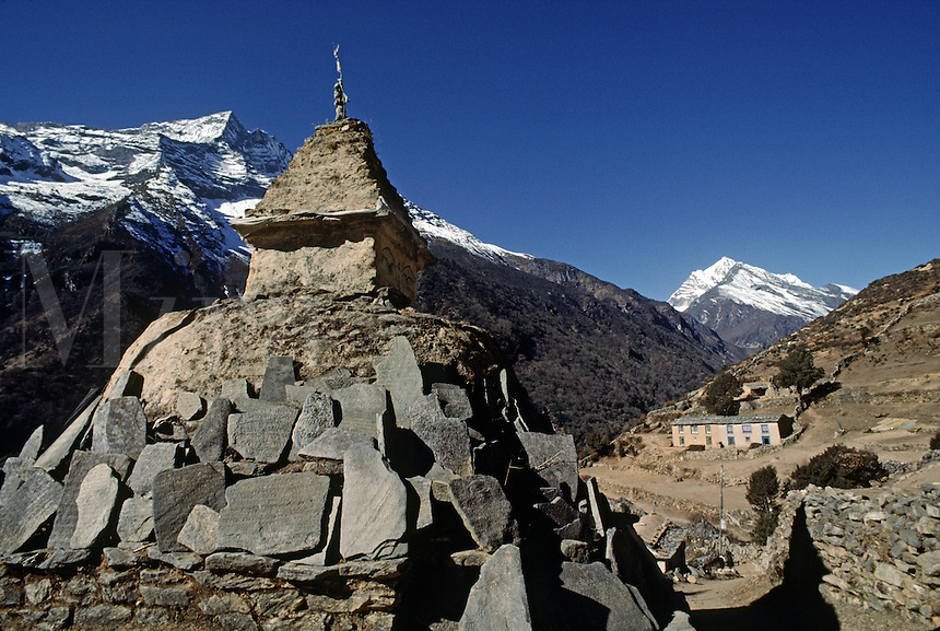 A TIBETAN BUDDHIST CHORTEN with MANI STONES on route to MOUNT EVEREST which is visiblebehind Lhotse - KHUMBU DISTRICT, NEPAL