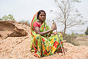 "India - Jharkhand - Dhab - A 22-year-old from Dhab, Gita Devi sits in the mica mine while holding the metal stick she uses to scrap the surface in search for mica. ""I started doing this job 10 years ago, together with the rest of my family"" she explains. ""I can make up to 20 kilos of mica per day, selling it at 10 rupees (0.15 USD) per kilo."" With the meagre income she earns, Devi is still able to buy food for the family and send her kids to school. But in the rainy season, she adds, nobody can mine, as mines are filled with water and can collapse anytime."
