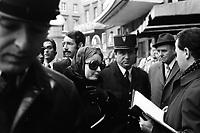 """Picard, Me Cathala, Me Bouscatel, Me Rastoul"""". Place Wilson. 30 novembre 1976. Vue d'ensemble de plusieurs personnes (plan taille) : au 1er plan visage d'un policier ; au 2nd plan femme (lunettes noires, foulard sur la tête), face à elle un homme de profil tient un dossier (juge d'instruction M. Ducasse?), derrière elle Christian Portay (un des acusés). Cliché pris le jour d'une reconstitution judiciaire dans le cadre de l'affaire du meurtre de René Trouvé. Observation: Affaire René Trouvé-Birague : le 19 février 1976, le journaliste René Trouvé est assassiné d'une balle dans la tête, par deux inconnus, alors qu'il regagne son domicile au 33 rue Bayard."""