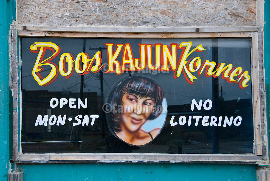 SIgns on the window and wall of Boos Kajun Korner-Open Mon-Sat No Loitering