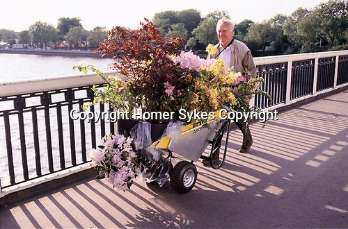 Chelsea Flowers Show last day taking home flowers sold cheaply at the end of the show London Uk 1997. Pushing flowers bought across Chelsea Bridge, and the car park on the other side.