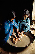 January 1979, Bolivia. Young girls working as kitchen help, clean a pig at a truck stop restaurant on the banks of the Titicaca region of Bolivia. Child labor as seen around the world between 1979 and 1980 - Photographer Jean Pierre Laffont, touched by the suffering of child workers, chronicled their plight in 12 countries over the course of one year.  Laffont was awarded The World Press Award and Madeline Ross Award among many others for his work.