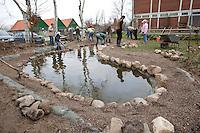 Grundschulklasse, Schulklasse legt einen Schulteich, Schul-Teich, Teich, Gartenteich, Garten-Teich im Schulgarten an, Kinder verteilen feinkörnigen Kies im Teich, der als Bodensubstrat für den neuangelegten Teich dient, die Uferumrandung wird mit Feldsteinen eingefasst