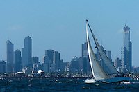 A crusing yacht enjoys an afternoon sail on the bay with the city of Melbourne Australia in the background